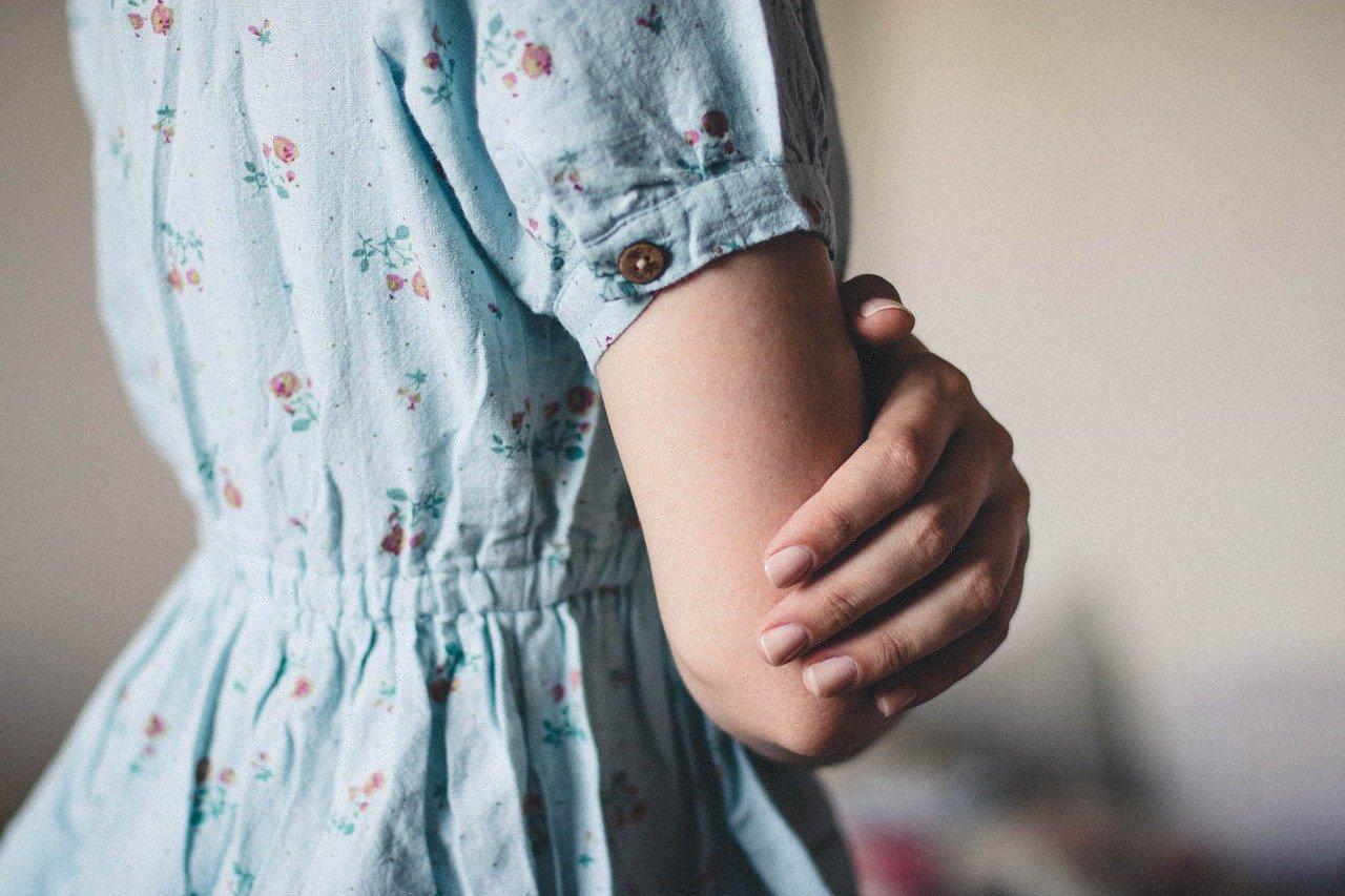 肘を抱く女性