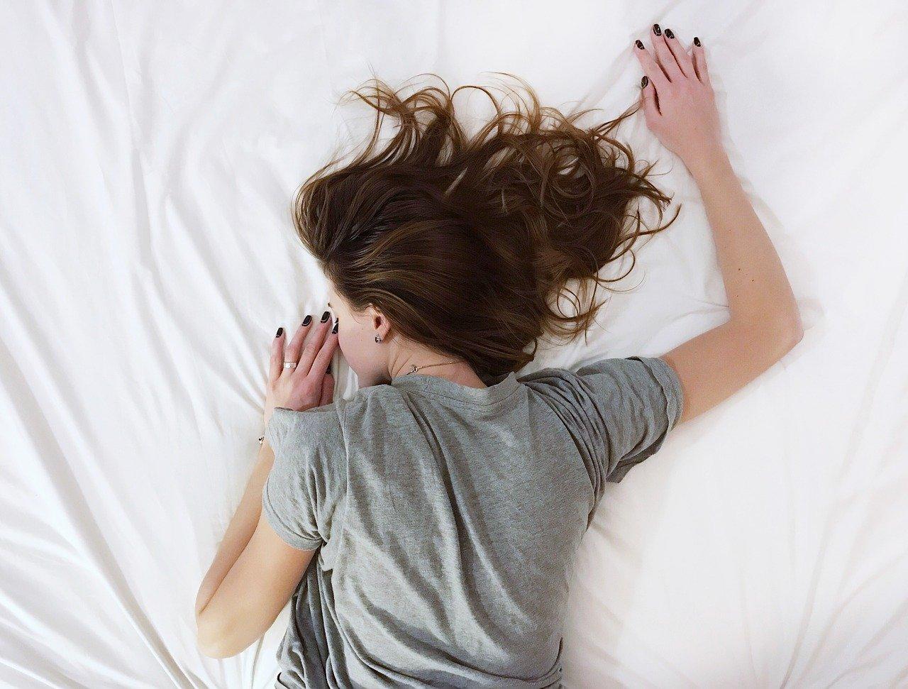 ベッドにうつぶせになる女性