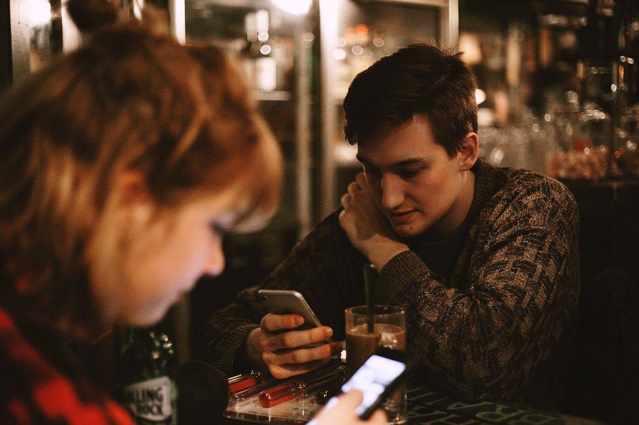 バーでスマホを見る男性
