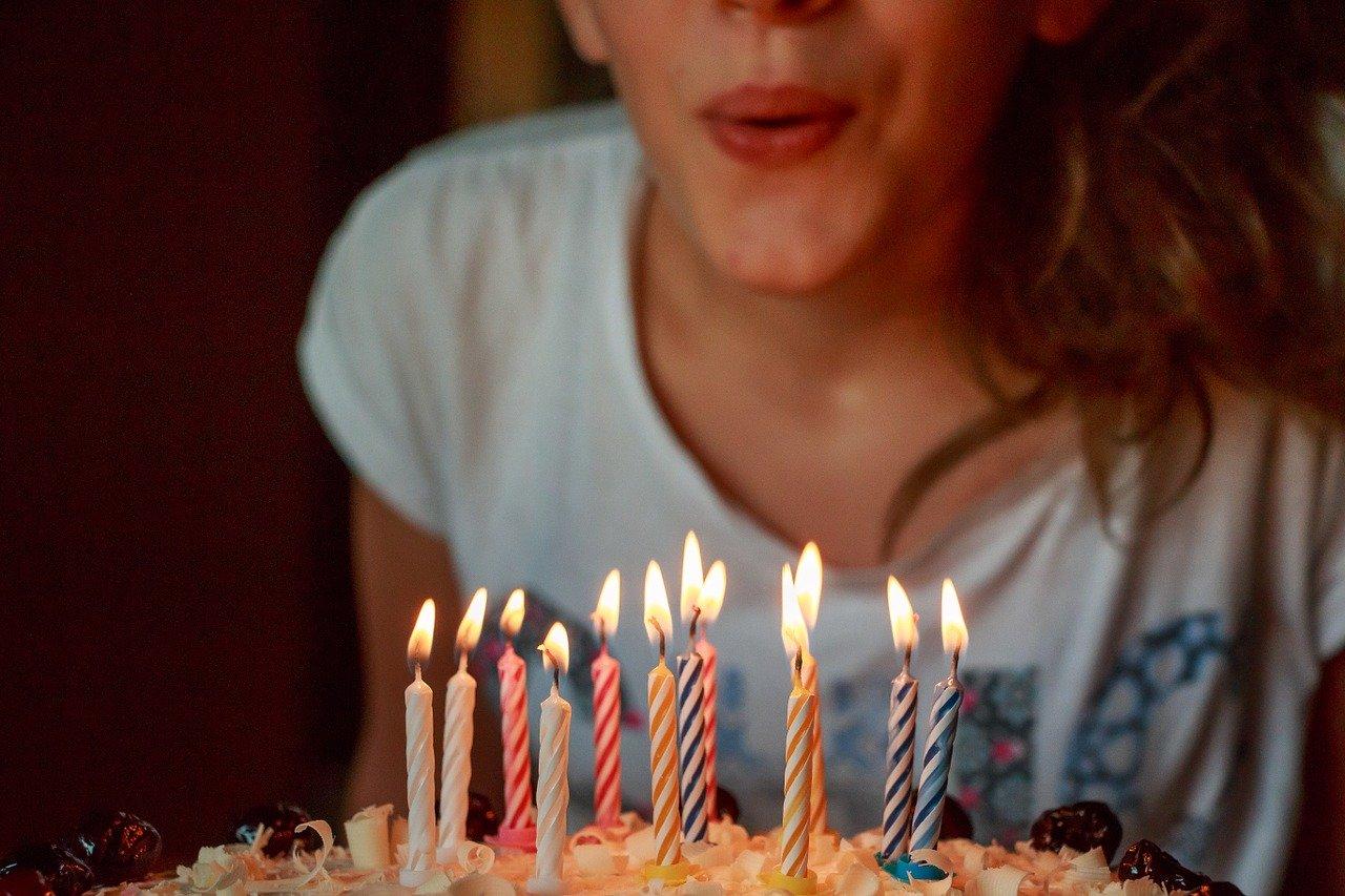誕生日ケーキの火を消す女性