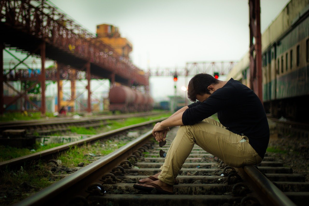 線路でうなだれる男性