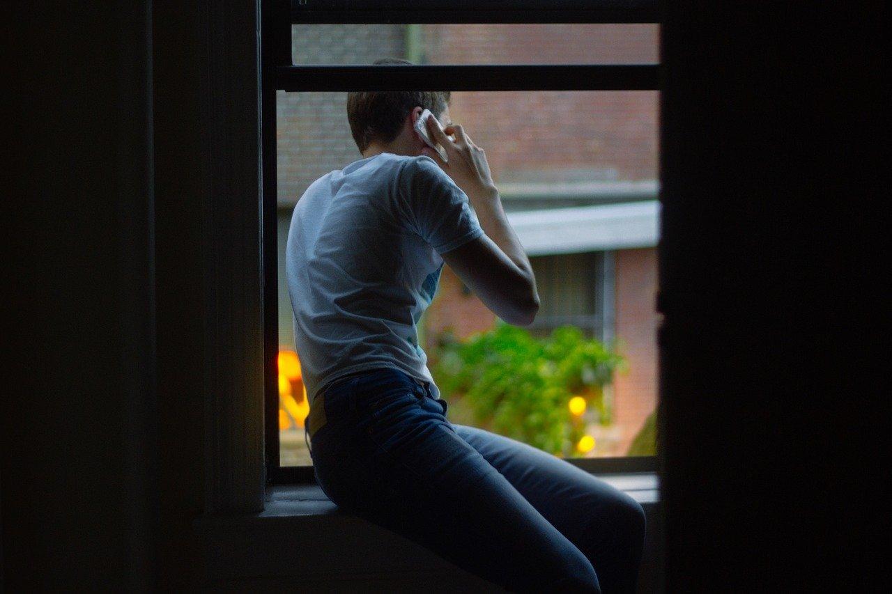 外を見ながら電話する男性