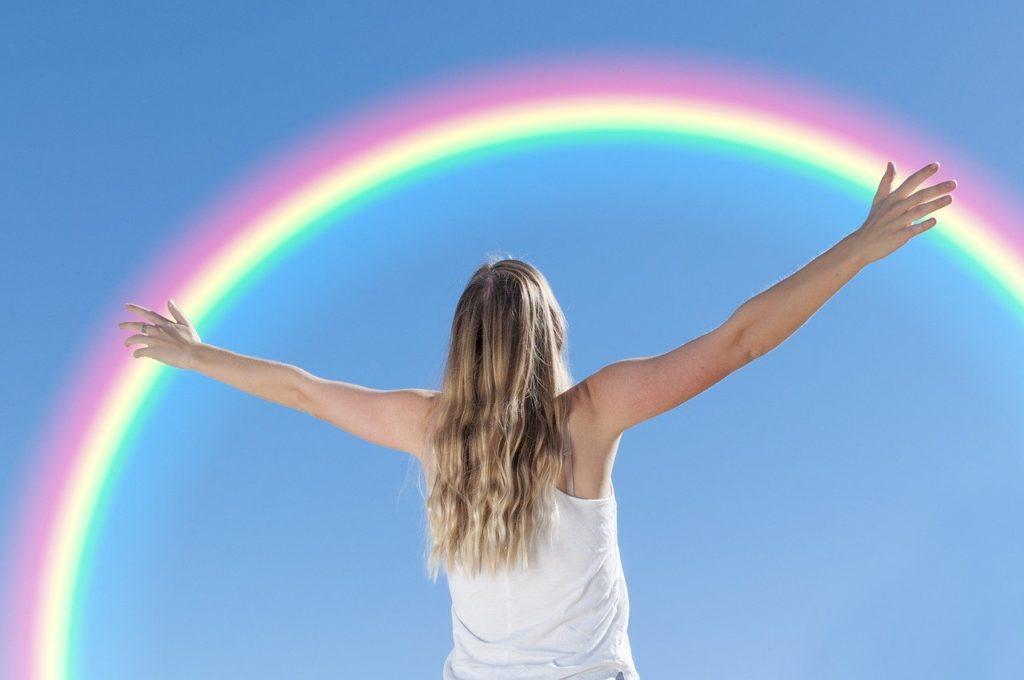 手を広げる女性と虹
